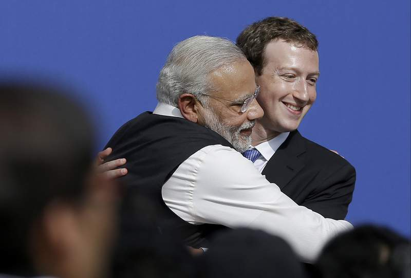 FILE - In this Sept. 27, 2015, file photo, Facebook CEO Mark Zuckerberg, right, hugs Prime Minister of India Narendra Modi at Facebook in Menlo Park, Calif. Members of India's governing party on Monday rejected allegations that Facebook had chosen to turn a blind eye to partisan hate speech on its platform to protect its growing business interests in India. As usage has spread across India, Facebook and its subsidiary WhatsApp have become fierce battlegrounds for Indias political parties, but spokesmen for Prime Minister Narendra Modis Bharatiya Janata Party denied a newspaper report that asserted Facebook officials chose not to take action against party members whose posts violated rules against hate speech. (AP Photo/Jeff Chiu, File)