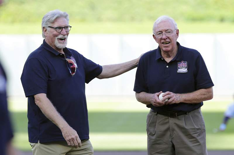 Former Minnesota Twins pitcher Jack Morris gives former Twins manager Tom Kelly the ball for the first pitch as the members of the 1991 Minnesota Twins World Series champions were honored before the baseball game between the Twins and Tampa Bay Rays, Saturday, Aug. 14, 2021, in Minneapolis. (AP Photo/Andy Clayton-King)