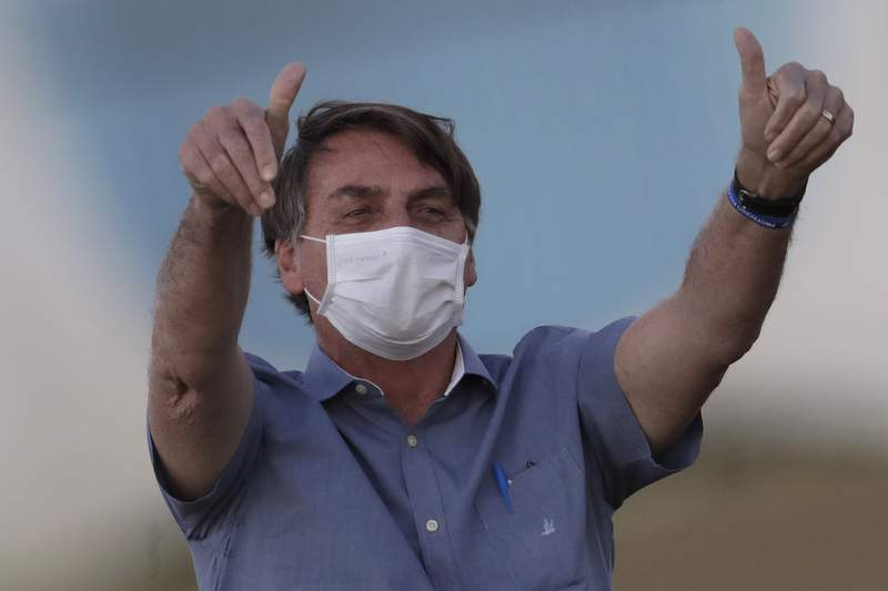 FILE - In this  July 17, 2020, file photo, Brazil's President Jair Bolsonaro who is infected with COVID-19, wears a protective face mask as he flashes thumbs-up at supporters during a Brazilian flag retreat ceremony outside his official residence Alvorada Palace, in Brasilia, Brazil. Bolsonaro announced his illness in July and used it to publicly extol hydroxychloroquine, the unproven malaria drug that hed been promoting as a treatment for COVID-19 and was taking himself. (AP Photo/Eraldo Peres, File)