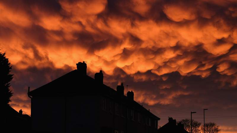 Mammatus clouds form over houses at sunset.