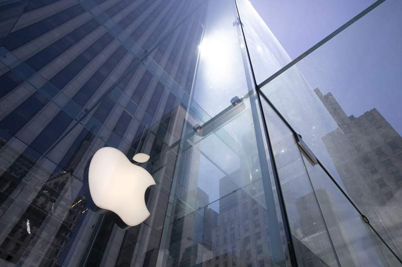 FILE - In this Tuesday, June 16, 2020 file photo, the sun is reflected on Apple's Fifth Avenue store in New York.  Apple has managed to shine amid the gloom, putting it on the cusp of becoming the first U.S. company to boast a market value of $2 trillion, just two years after it became the first to reach $1 trillion. With its stock already up 50% this year, the only question among analysts is whether Apple will pass the $2 trillion milestone before the release of its next-generation iPhones in October.(AP Photo/Mark Lennihan, File)