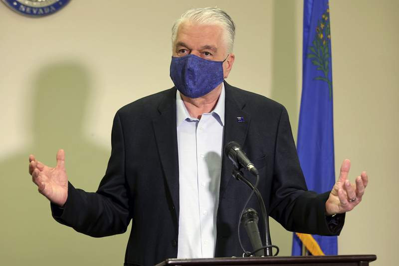 FILE - In this Friday, Oct. 2, 2020 file photo Nevada Gov. Steve Sisolak updates the state's COVID-19 response during a news conference at the Sawyer Building in Las Vegas. Nevada Gov. Steve Sisolak said that he had tested positive for COVID-19 on Friday, Nov. 13, 2020 as the virus surges to record levels in Nevada and throughout the United States.(K.M. Cannon/Las Vegas Review-Journal via AP, Pool, File)