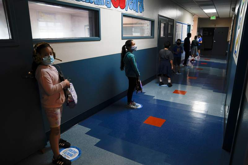 """Los Angeles Unified School District students stand in a hallway socially distance during a lunch break at Boys & Girls Club of Hollywood in Los Angeles, Wednesday, Aug. 26, 2020. The LAUSD schools resumed classes with distance learning, but many underprivileged students still struggle, according to Mel Culpepper, CEO of Boys & Girls Club of Hollywood. The facility is open for children whose parents must leave home to work. There is no charge. Snacks and lunch are provided. """"These kids are already behind,"""" said Culpepper. """"Our mission is to help the kids and families that need us most and that's what we are doing."""" (AP Photo/Jae C. Hong)"""