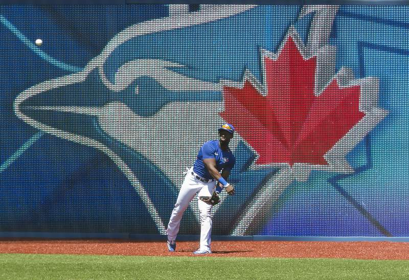 Toronto Blue Jays outfielder Jonathan Davis throws the ball back after making a catch during live batting practice at baseball training camp in Toronto on Monday, July 20, 2020. (Nathan Denette/The Canadian Press via AP)