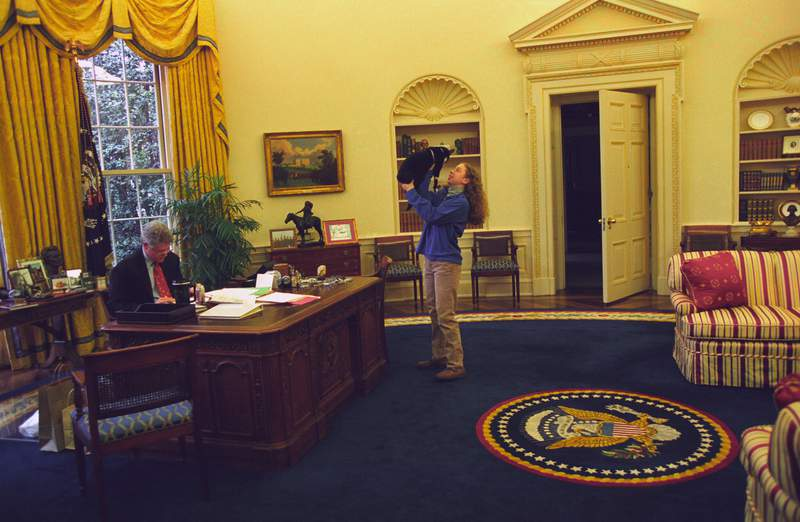 President Bill Clinton works at his desk in the Oval Office, with First Daughter Chelsea Clinton in 1994.