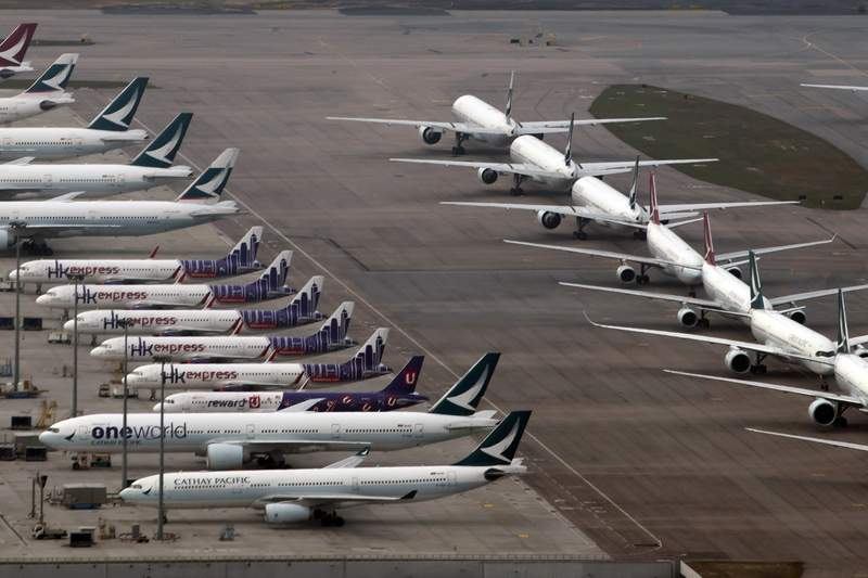 Cathay Pacific and Hong Kong Express aircrafts line up on the tarmac at the Hong Kong International Airport, Friday, March 6, 2020. The global airline's flying schedules have declined since the outbreak of new coronavirus COVID-19. (AP Photo/Kin Cheung)