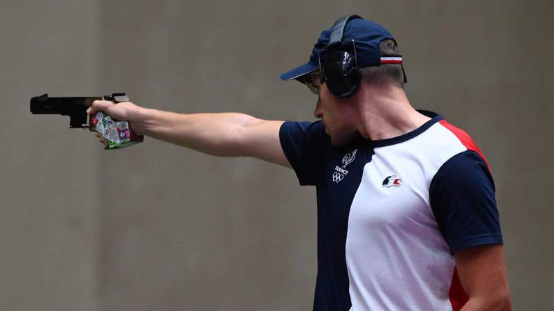 Jean Quiquampoix fires at targets in the men's rapid-fire pistol event.
