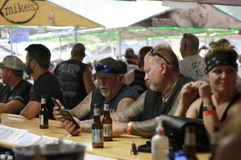 People congregates at One-Eyed Jack's Saloon during the 80th annual Sturgis Motorcycle Rally on Aug. 7, 2020, in Sturgis, South Dakota. The South Dakota Department of Health issued warnings that two people who had visited the bar may have transmitted COVID-19. (AP Photo/Stephen Groves)