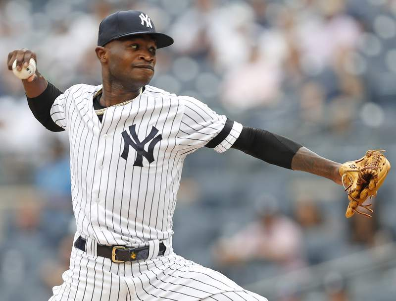 FILE - In this July 18, 2019, file photo, New York Yankees' starting pitcher Domingo German winds up during the first inning in the first game of a baseball doubleheader in New York. Suspended Yankees pitcher German cast doubt on his baseball future with a curious Instagram post Friday, July 17, 2020, night. (AP Photo/Kathy Willens, File)