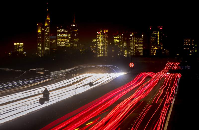 A long time exposure photo shows cars and trucks driving on a highway near Frankfurt, Germany, Tuesday, Nov. 17, 2020. In background the buildings of the banking district. (AP Photo/Michael Probst)