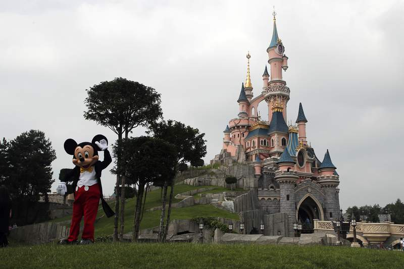 FILE - In this June 8, 2018 file photo, Mickey Mouse poses in front of the castle of Sleeping Beauty at Disneyland Paris, in Chessy, France, east of Paris. Theme parks at Walt Disney World Resort in Florida and Disneyland Paris Resort will be closing through the end of the month, starting at the close of business Sunday, the Walt Disney Company announced. For most people, the new coronavirus causes only mild or moderate symptoms. For some it can cause more severe illness. (AP Photo/Francois Mori, File)