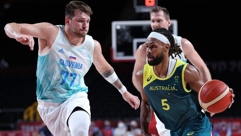 Australia's Patty Mills (R) dribbles the ball past Slovenia's Luka Doncic (L) and Zoran Dragic in the men's bronze medal basketball match between Slovenia and Australia during the Tokyo 2020 Olympic Games at the Saitama Super Arena in Saitama on August 7, 2021.