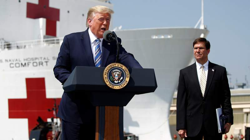 President Donald Trump speaks in front of the U.S. Navy hospital ship USNS Comfort at Naval Station Norfolk in Norfolk, Va., Saturday, March 28, 2020. The ship is departing for New York to assist hospitals responding to the coronavirus outbreak. Defense Secretary Mark Esper is at right. (AP Photo/Patrick Semansky)