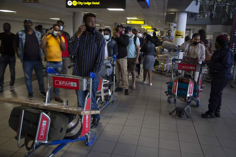 FILE  In this Oct.1, 2020 file photo passengers queue to access the O.R. Tambo Airport in Johannesburg, South African travel agencies are reporting a surge in reservations for travel to and from Britain ahead of the country being removed from the U.K.'s COVID-19 red list next week. (AP Photo/Denis Farrell/File)