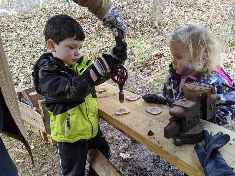 Kids make crafts using wood from the forest.