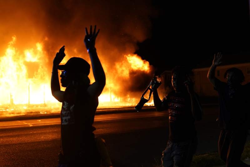 FILE - In this Aug. 24, 2020, file photo, protesters walk past police with their arms up, in Kenosha, Wis., as a building burns in the background. Protests have erupted following the police shooting of Jacob Blake a day earlier. Kenosha police say 55 people are facing charges related to violent demonstrations after the police shooting of Jacob Blake last summer. (AP Photo/David Goldman, File)