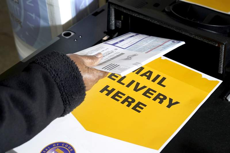 A Cook County, Ill., resident drops off her mail-in ballot Tuesday, Oct. 13, 2020, at a county courthouse in Maywood, Ill. (AP Photo/Charles Rex Arbogast)