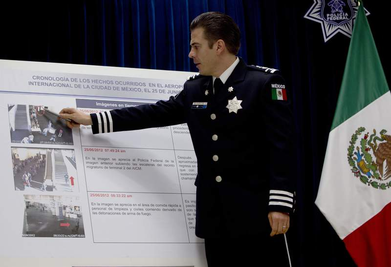 FILE - In this June 28, 2012 file photo, Luis Cardenas Palomino, chief of the regional security division of Mexico's federal police, points to surveillance camera footage at the international airport related to a shooting, during a press conference in Mexico City. Mexico said Monday, July 5, 2021, that it has arrested the former leading police officers on charges of torture from nearly a decade ago.  (AP Photo/Esteban Felix, File)