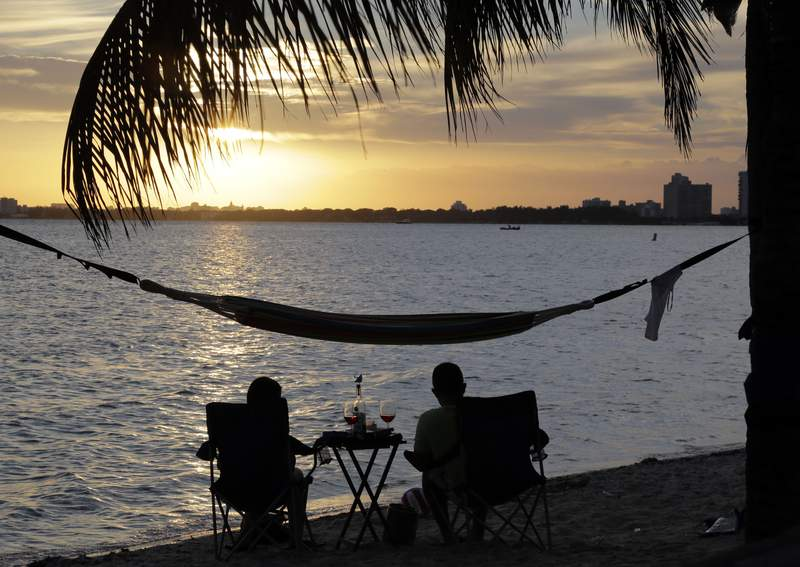 FILE - In this Thursday, April 16, 2015, file photo, a couple watches the sunset over Biscayne Bay from a beach in Key Biscayne, Fla. Older adults who are childless in the U.S. are more like to be college educated, in the workforce at a greater rate and are more readily non-Hispanic white than those with children, and their numbers are growing, according to a new Census Bureau report released Tuesday, Aug. 31, 2021. (AP Photo/Lynne Sladky, File)