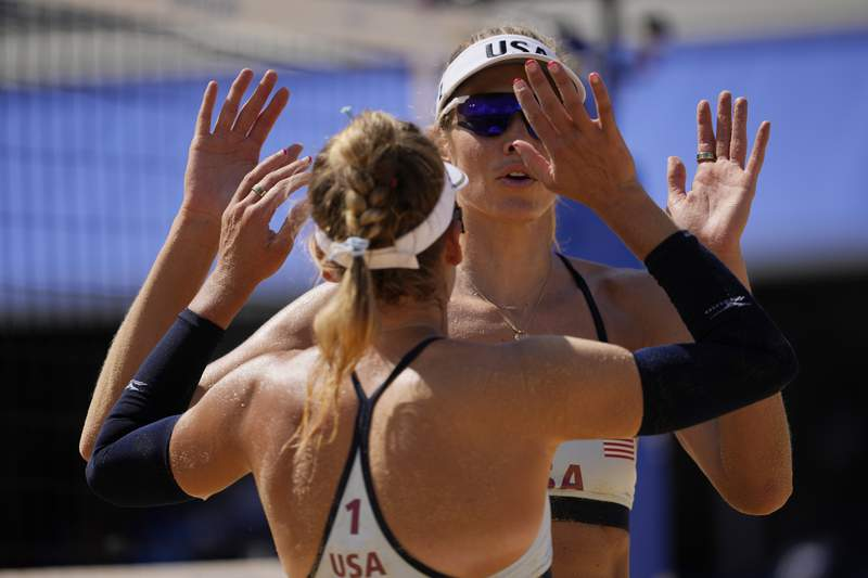 April Ross, left, of the United States, greets teammate, Alex Klineman, during a woman's beach volleyball match against China at the 2020 Summer Olympics, Sunday, July 25, 2021, in Tokyo, Japan. (AP Photo/Petros Giannakouris)