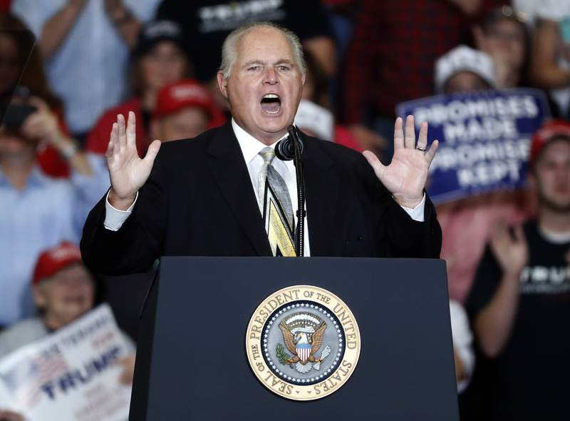 FILE - Radio personality Rush Limbaugh introduces President Donald Trump at the start of a campaign rally on Nov. 5, 2018, in Cape Girardeau, Mo. Limbaugh's radio syndicators say they plan to keep his voice alive. Premiere Networks said on Monday, March 22, 2021, that Limbaugh's show will continue with its present format, where a series of guest hosts introduce archival audio footage of his voice. Limbaugh died of cancer on Feb. 17. (AP Photo/Jeff Roberson, File)