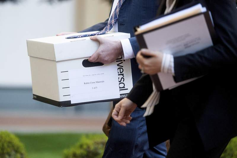 Legal workers carry documents for the Epic Games vs. Apple federal court case into the Ronald V. Dellums building in Oakland, Calif. Epic, maker of the video game Fortnite, charges that Apple has transformed its App Store into an illegal monopoly. (AP Photo/Noah Berger)