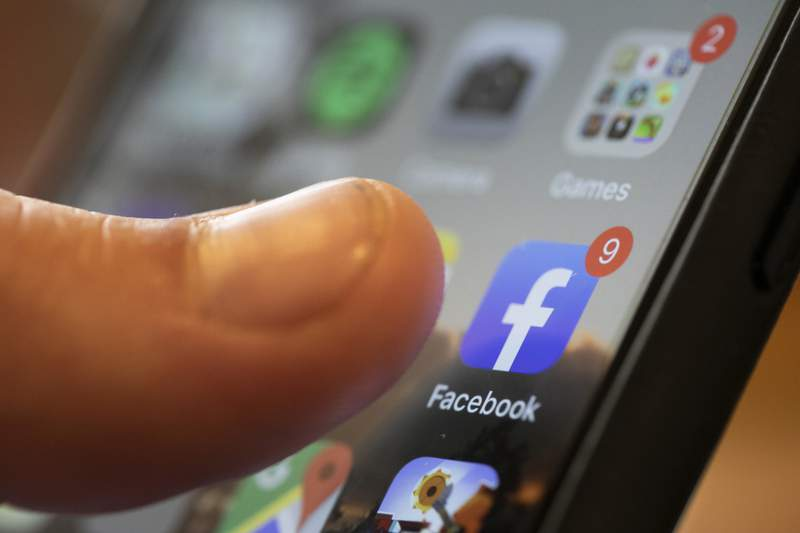 FILE - In this Aug. 11, 2019, file photo, an iPhone displays the Facebook app in New Orleans. Users across the northeast U.S. reported widespread internet outages Tuesday, Jan. 26, 2021. Verizon reported a fiber cut in Brooklyn via Twitter, although its not clear if that issue is responsible for the entire outage. According to DownDetector and user reports on Twitter, the problem appears to extend from Washington to Boston, and is affecting internet and cloud providers as well as a number of Google services, Facebook and other major sites. (AP Photo/Jenny Kane, File)