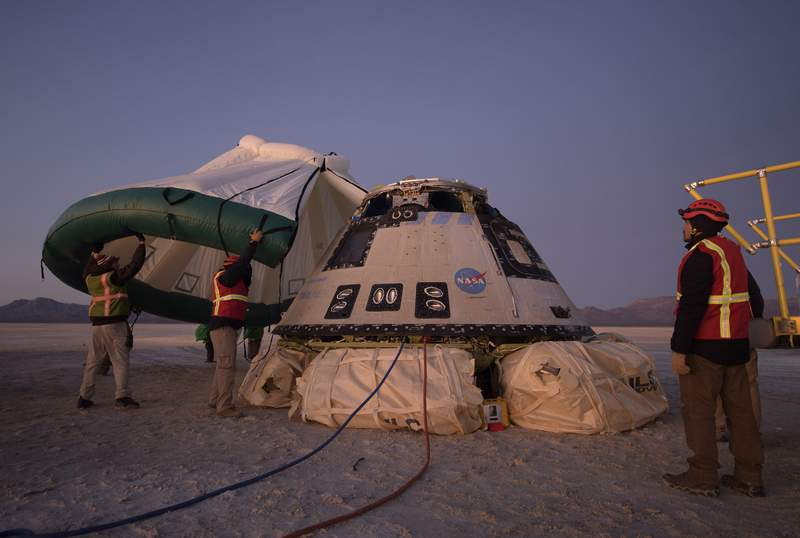 FILE - In this Sunday, Dec. 22, 2019 photo made available by NASA, Boeing, NASA, and U.S. Army personnel work around the Boeing Starliner spacecraft shortly after it landed in White Sands, N.M. On Friday, Feb. 7, 2020, NASA said defective software could have doomed the crew capsule during its first test flight that ended up being cut short. (Bill Ingalls/NASA via AP)