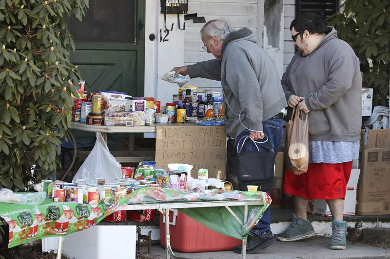 Two residents select items on a community table, filled with groceries for those in need, in Derry, N.H., Wednesday, March 18, 2020. The table was started as part of a local Facebook group, reaching out to residents that are impacted by the virus outbreak and the quick slowdown in the economy. For most people, the new coronavirus causes only mild or moderate symptoms. For some, it can cause more severe illness, especially in older adults and people with existing health problems. (AP Photo/Charles Krupa)