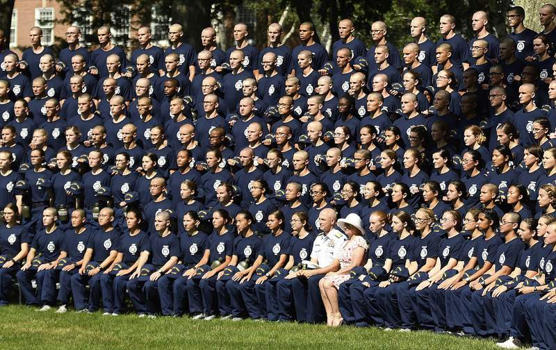 FILE - In a Monday, July 1, 2019 file photo, U.S. Coast Guard Academy Superintendent Rear Adm. William G. Kelly and his wife Angie pose with the Class of 2023 for their class photo on Day One of Swab Summer in New London, Conn. The Department of Homeland Securitys inspector general says the U.S. Coast Guard Academy has failed to properly investigate and handle allegations of racial harassment, including the use of racial slurs by cadets.  (Sean D. Elliot/The Day via AP, File)