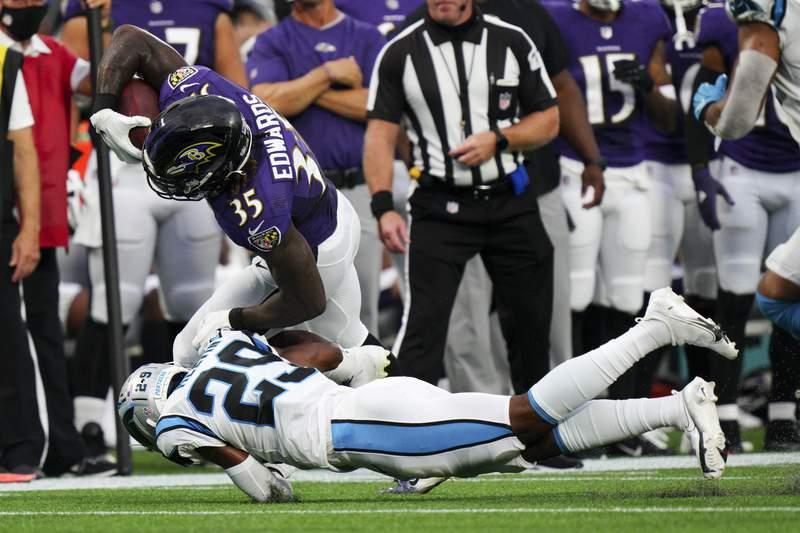 Baltimore Ravens running back Gus Edwards is tackled by Carolina Panthers cornerback Rashaan Melvin during the first half of a preseason NFL football game Saturday, Aug. 21, 2021, in Charlotte, N.C. (AP Photo/Jacob Kupferman)