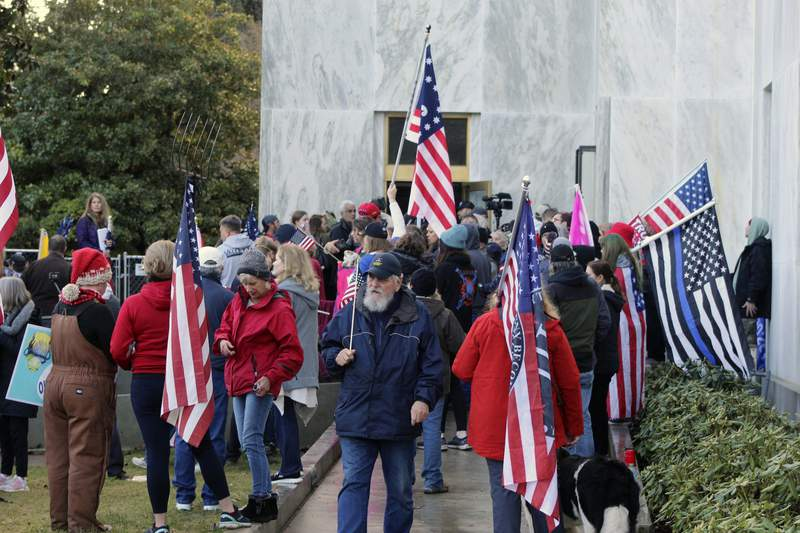 FILE - In this Dec. 21, 2020, file photo, pro-Trump and anti-mask demonstrators hold a rally outside the Oregon State Capitol as legislators meet for an emergency session in Salem, Ore. During the protest Republican lawmaker, Rep. Mike Nearman, physically opened the Capitol's door  letting protesters, who clashed with police, gain access to the building. There have been calls for Nearman to resign ahead of the upcoming 2021 Legislative session that begins Tuesday, Jan. 19, 2021. (AP Photo/Andrew Selsky, File)
