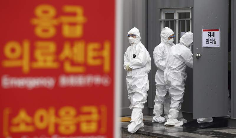 """Officials wearing protective attire work to diagnose people with suspected symptoms of the new coronavirus at a hospital in Daegu, South Korea, Wednesday, Feb. 26, 2020. The number of new virus infections in South Korea jumped again Wednesday and the U.S. military reported its first case among its soldiers based in the Asian country, with his case and many others connected to a southeastern city with an illness cluster. A sign reads """"Emergency Medical Center."""" (Kim Hyun-tae/Yonhap via AP)"""