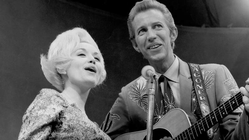 Country singer Dolly Parton and her collaborator Porter Wagoner perform onstage in circa 1967.