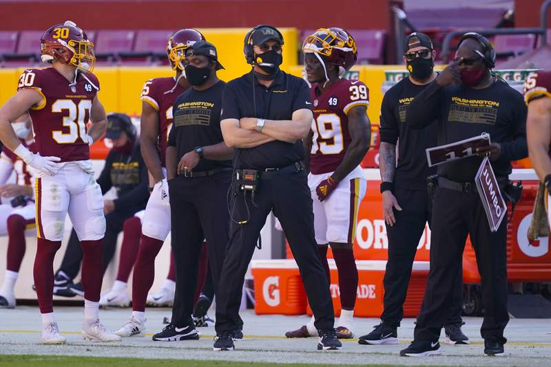 Washington Football Team head coach Ron Rivera, center, crossing his arms as he waits for game action to resume during the first half of an NFL football game against the New York Giants, Sunday, Nov. 8, 2020, in Landover, Md. (AP Photo/Al Drago)