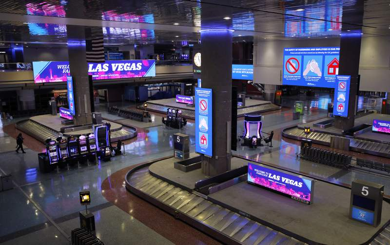 In this April 21, 2020, photo, electric signs that usually advertise casinos and other entertainment now give tips on preventing the spread of the coronavirus at McCarran International airport in Las Vegas. Nevada's governor shuttered the glitzy casinos and nightlife attractions of Las Vegas in mid-March, leaving much of the famous gambling mecca empty. (AP Photo/John Locher)