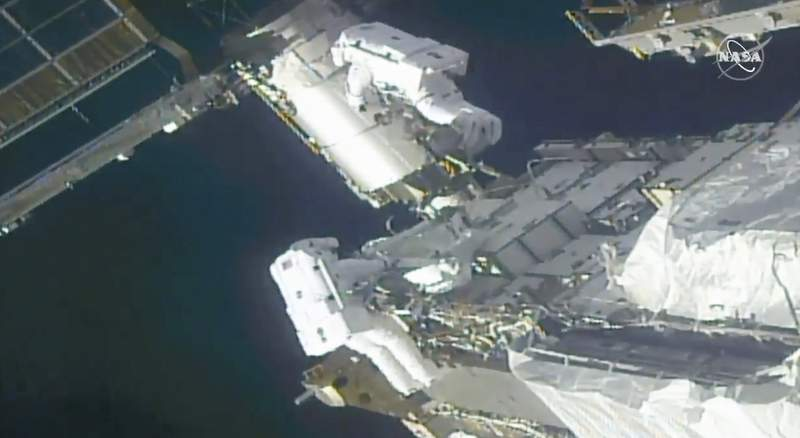 In this image taken from NASA video, NASA astronauts Kate Rubins, top, and Victor Glover work outside the International Space Station Sunday, Feb. 28, 2021. The  spacewalking astronauts ventured out Sunday to install support frames for new, high-efficiency solar panels arriving at the International Space Station later this year.  (NASA via AP)