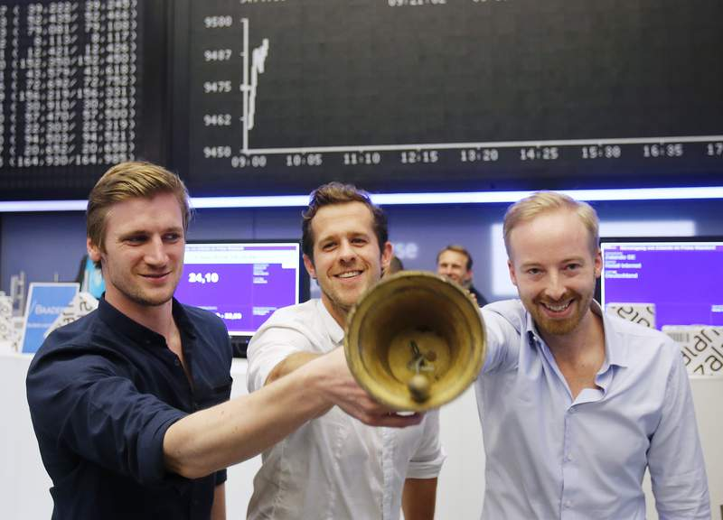 FILE - In this Jan. 10, 2014 file photo, the three CEOs of German online warehouse Zalando, David Schneider, Robert Gentz and Rubin Ritter, from left, ring the bell during the company's initial public offering at the stock market in Frankfurt, Germany. The chief executive of online fashion retailer Zalando Rubin Ritter is stepping down to focus on his family, saying his wifes career should take priority in the coming years. Ritter has been one of three chief executives at Zalando since 2010. (AP Photo/Michael Probst, File)