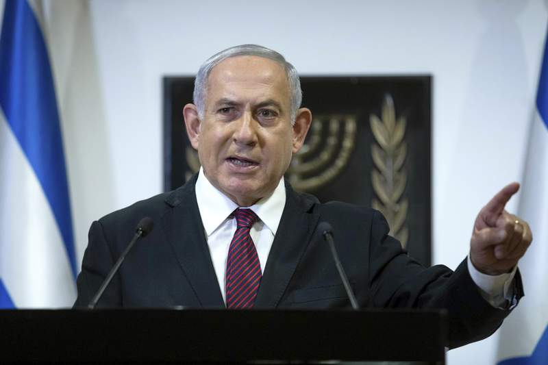 FILE - In this Dec. 22, 2020 file photo, Israeli Prime Minister Benjamin Netanyahu delivers a statement at the Israeli Knesset, or Parliament, in Jerusalem. Israeli prosecutors on Sunday , Jan. 3, 2021, released an amended indictment spelling out detailed charges against Netanyahu in a corruption case in which he is accused of trading favors with a powerful media mogul.  (Yonatan Sindel/Pool Photo via AP, File)