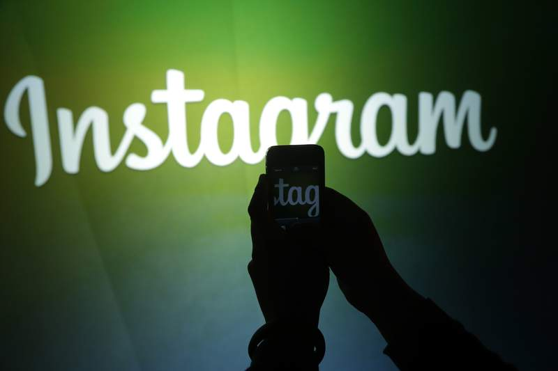 FILE - In this June 20, 2013 file photo, a journalist makes a video of the Instagram logo using the new video feature at Facebook headquarters in Menlo Park, Calif. British regulators said Friday, Oct. 16, 2020 that Instagram will clamp down on hidden advertising by social media influencers. The Competition and Markets Authority said  that Instagram's owner Facebook has committed to tightening up policies to restrict influencers who dont disclose theyre being paid to promote businesses on its platform. (AP Photo/Marcio Jose Sanchez, File)