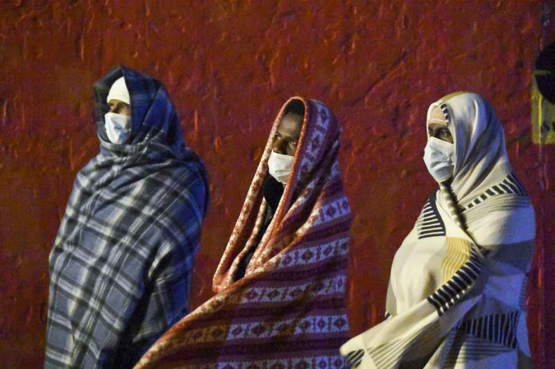 FILE - In this Tuesday, May 11, 2021, file photo, migrants, wearing face masks to help curb the spread of COVID-19, stand on the tug boat Asso Trenta bringing them back to land after their transfer to a bigger ship was aborted due to rough sea conditions in Lampedusa, Sicily, Italy. The European Union's asylum agency said Tuesday June 29, 2021, that the number of people seeking international protection in Europe hit its lowest level last year since 2013, but that the drop was due mostly to coronavirus travel restrictions. (AP Photo/Salvatore Cavalli, File)