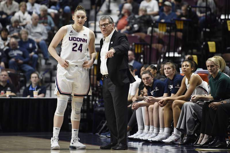 FILE - In this March 7, 2020, file photo, Connecticut head coach Geno Auriemma talks with Connecticut's Anna Makurat (24) in the first half of an NCAA college basketball game in the American Athletic Conference tournament quarterfinals at Mohegan Sun Arena in Uncasville, Conn. Auriemma is asking for help from Congress to get foreign students, including athletes, back to campus. The Huskies have three foreign players on their roster this year: Anna Makurat, a sophomore from Poland; Nika Muhl, a freshman from Croatia, and Aaliyah Edwards, a freshman from Ontario, Canada. (AP Photo/Jessica Hill, File)