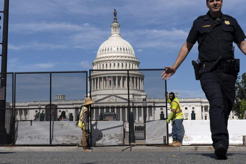 U.S. Capitol police officer push back people who are watching workers remove the fence surrounding the U.S. Capitol building, after six months was erected, following the Jan. 6 riot at the Capitol, on Saturday, July 10, 2021, in Washington. (AP Photo/Jose Luis Magana)