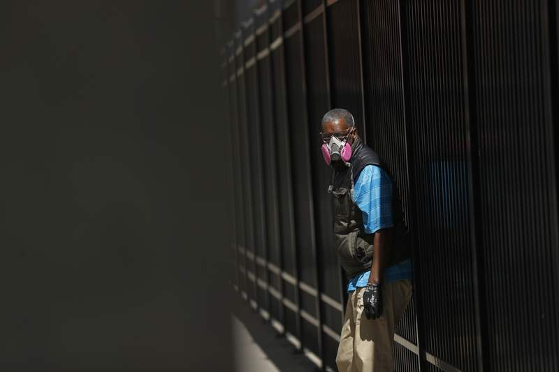 A man wears a protective mask while waiting for a bus in Detroit, Wednesday, April 8, 2020. As of mid April 2020, it's not yet clear how often people can spread the COVID-19 coronavirus without showing symptoms. (AP Photo/Paul Sancya)