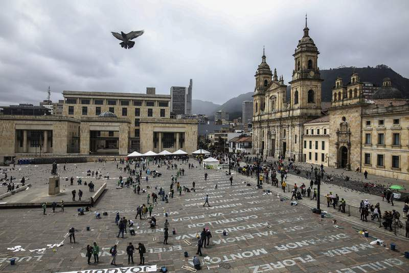 FILE - This June 10, 2019 file photo shows activists who have received death threats displaying the names of killed leftist activists as part of an art installation by Colombia artist Doris Salcedo at Plaza Bolivar in downtown Bogota, Colombia. Slayings of human rights leaders and mass killings of civilians are increasing at a worrying pace in Colombia, according to a United Nations report published on Tuesday, Feb. 23, 2021. (AP Photo/Ivan Valencia, File)