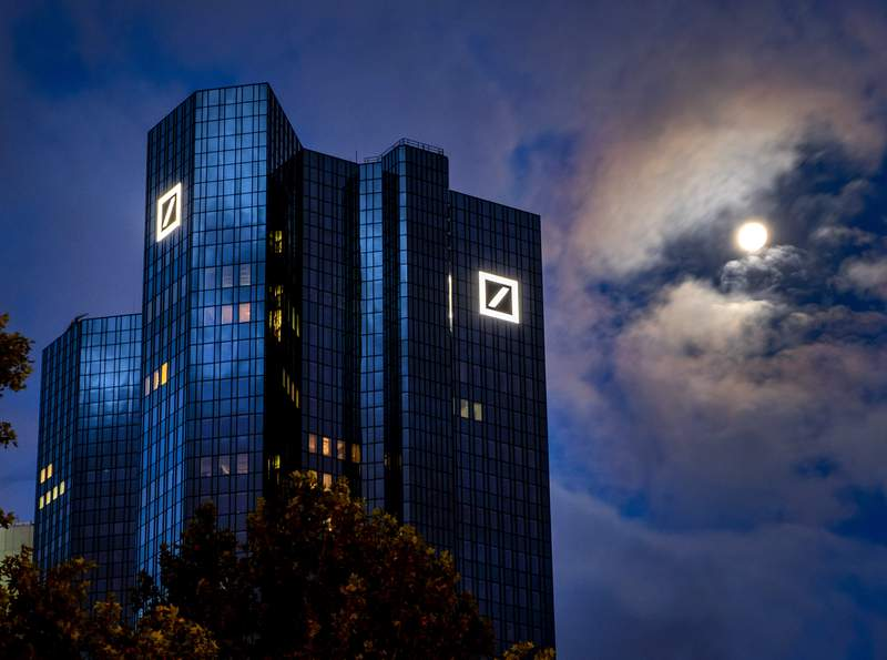 The moon shines next to the headquarters of the Deutsche Bank in Frankfurt, Germany, early Sunday, Oct. 4, 2020. (AP Photo/Michael Probst)