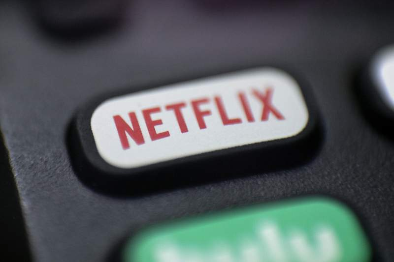 FILE - This Aug. 13, 2020 photo shows a logo for Netflix on a remote control in Portland, Ore.  Netflixs rapid subscriber growth is slowing far faster than anticipated, Tuesday, April 20, 2021, as people who have been cooped at home during the pandemic are able to get out and do other things again. The video streaming service added 4 million more worldwide subscribers from January through March, its smallest gain during that three-month period in four years.   (AP Photo/Jenny Kane, File)