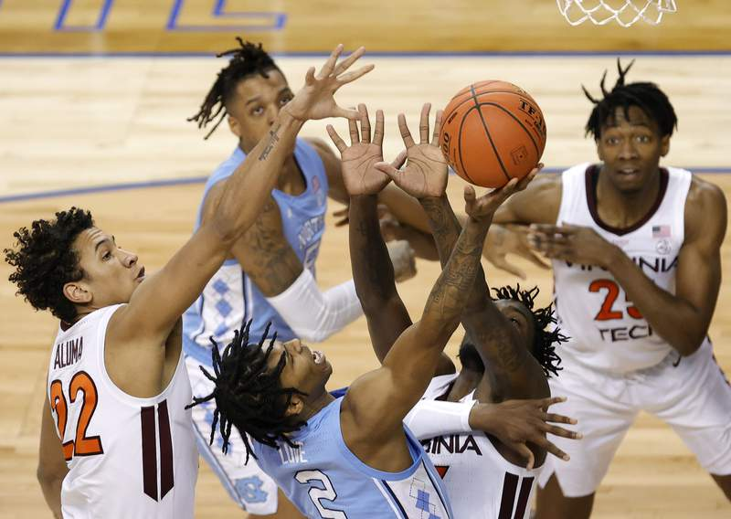 GREENSBORO, NORTH CAROLINA - MARCH 11: Caleb Love #2 of the North Carolina Tar Heels attempts a shot against Tyrece Radford #23 and Keve Aluma #22 of the Virginia Tech Hokies during the second half of their quarterfinals game in the ACC Men's Basketball Tournament at Greensboro Coliseum on March 11, 2021 in Greensboro, North Carolina. (Photo by Jared C. Tilton/Getty Images)