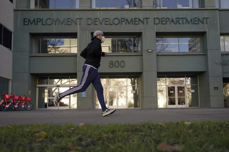 FILE  In his Dec. 18, 2020 file photo a runner passes the office of the California Employment Development Department in Sacramento, Calif. California reported a significant surge in unemployment claims last week for independent contractors, accounting for more than a quarter of all such climbs nationally and raising concerns about a return of widespread fraud, Thursday, Jan. 21, 2021. (AP Photo/Rich Pedroncelli, File)