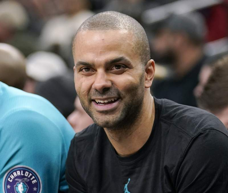 FILE - In this Jan. 14, 2019 file photo, Charlotte Hornets' Tony Parker laughs on the bench during the second half of an NBA basketball game against the San Antonio Spurs, in San Antonio. Europe's elite basketball league features teams from 10 countries navigating COVID-19 cases, international travel restrictions and last-minute postponements. NBA great Tony Parker's French team has played just half of its scheduled games in the EuroLeague and the chaotic start prompted Milan coach Ettore Messina on Monday Nov. 2, 2020, to call for suspending the season until March or April. (AP Photo/Darren Abate, File)